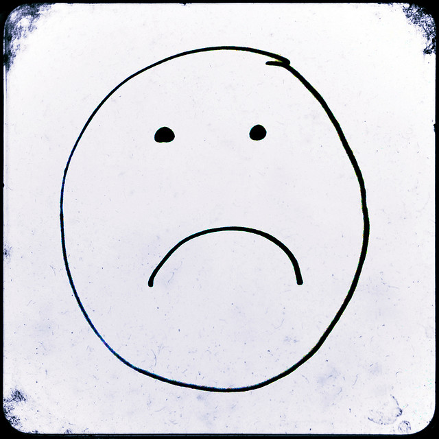 """TTV photograph of a frownie face drawn with marker on paper"""