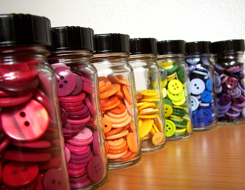 """row of jars filled with brightly colored buttons"""